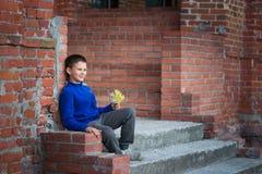 Adolescente del muchacho que se sienta en el pórtico en casa Fotos de archivo libres de regalías