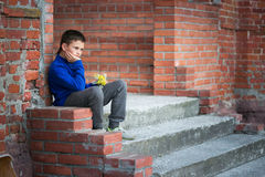 Adolescente del muchacho que se sienta en el pórtico en casa Imágenes de archivo libres de regalías