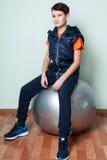 Adolescente del muchacho que se sienta en fitball Niño de la aptitud en ropa de deportes Imágenes de archivo libres de regalías