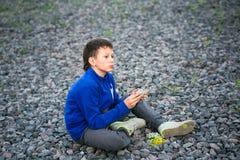 Adolescente del muchacho que se sienta en la grava con el ramo Imagen de archivo