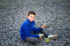 Adolescente del muchacho que se sienta en la grava con el ramo Imagenes de archivo
