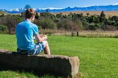 Adolescente del muchacho que sienta las montañas escénicas Imagen de archivo libre de regalías