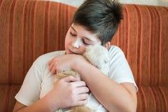 Adolescente del muchacho que sostiene el gatito en sus brazos Fotos de archivo