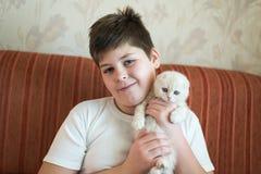 Adolescente del muchacho que sostiene el gatito en sus brazos Imágenes de archivo libres de regalías