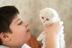 Adolescente del muchacho que sostiene el gatito en sus brazos Fotos de archivo libres de regalías