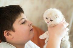 Adolescente del muchacho que sostiene el gatito en sus brazos Foto de archivo