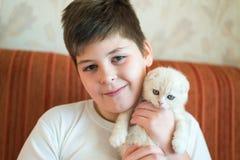 Adolescente del muchacho que sostiene el gatito en sus brazos Imagen de archivo libre de regalías