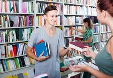 Adolescente del muchacho que toma el nuevo libro del vendedor en librería Fotografía de archivo