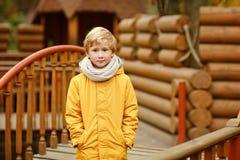 Adolescente del niño pequeño en una chaqueta amarilla en el otoño en un backgr Fotografía de archivo
