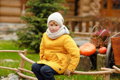 Adolescente del niño pequeño en una chaqueta amarilla en el otoño en un backgr Fotografía de archivo libre de regalías