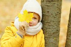 Adolescente del niño pequeño en una chaqueta amarilla en la caída, cerrando uno Imagenes de archivo