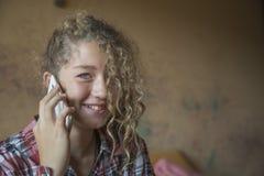 Adolescente del pelirrojo que habla en un teléfono móvil Foto de archivo
