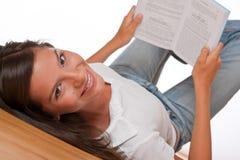 Adolescente del pelo de Brown que miente hacia abajo sujetando el libro Foto de archivo libre de regalías