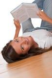 Adolescente del pelo de Brown que se acuesta en suelo de madera Imagenes de archivo