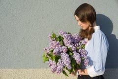 Adolescente del perfil con el ramo de lilas Foto de archivo libre de regalías