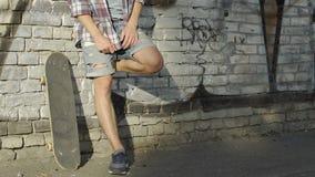 Adolescente del ragazzo che ascolta la musica con il pattino sul fondo della parete, nuova generazione stock footage