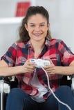 Adolescente del retrato en la silla de ruedas que juega al juego de ordenador Fotos de archivo libres de regalías