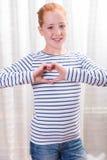 Adolescente del retrato que forma forma del corazón con las manos Imágenes de archivo libres de regalías