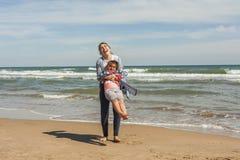 Adolescente del tiro lleno y su pequeña hermana que juegan en el shor del mar Imagen de archivo libre de regalías