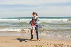 Adolescente del tiro lleno y su pequeña hermana que juegan en el shor del mar Fotografía de archivo