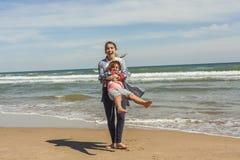 Adolescente del tiro lleno y su pequeña hermana que juegan en el shor del mar Fotografía de archivo libre de regalías
