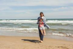Adolescente del tiro lleno y su pequeña hermana que juegan en el shor del mar Fotos de archivo