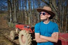 Adolescente del vaquero que se coloca cerca del tractor Foto de archivo libre de regalías
