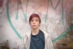 Adolescente delante de una pintada Foto de archivo