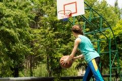 Adolescente delgado deportivo que juega a baloncesto Imágenes de archivo libres de regalías