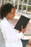 adolescente della lettura della ragazza del libro dell'afroamericano Fotografie Stock