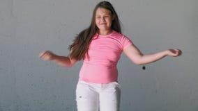 Adolescente della ragazza che balla su un fondo grigio Ballo della via stock footage