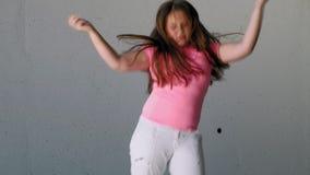 Adolescente della ragazza che balla su un fondo grigio Ballo della via video d archivio