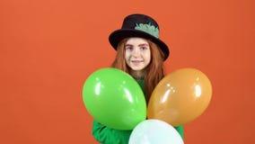 Adolescente della ragazza che celebra giorno del ` s di San Patrizio sulla parete arancio che tiene tre palloni stock footage