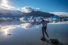 Adolescente della ragazza che salta sopra le rocce nel confine del lago del ghiacciaio di Fjallsarlon che affronta al sole L'Isla immagini stock