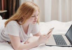Adolescente della ragazza con il computer portatile a letto Immagini Stock Libere da Diritti