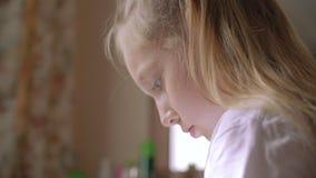 Adolescente della ragazza del ritratto che legge qualche cosa di vista laterale Ragazza del fronte nel profilo che esamina lo sch stock footage