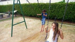 Adolescente della ragazza e del ragazzo che oscilla su un'oscillazione con i piedi nudi sul prato inglese verde del cortile della archivi video