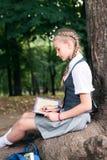 Adolescente della scolara che legge un libro in un parco vicino ad un albero fotografia stock libera da diritti
