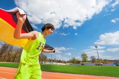 Adolescente deportivo que corre con la bandera de Alemania Imágenes de archivo libres de regalías