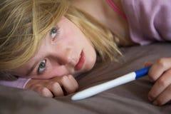 Adolescente deprimido que se sienta en dormitorio Foto de archivo