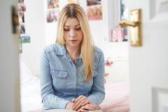 Adolescente deprimido que se sienta en dormitorio Imagenes de archivo