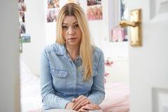 Adolescente deprimido que se sienta en dormitorio Imagen de archivo