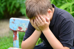 Adolescente deprimido que se sienta en el banco Imagen de archivo