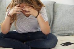 Adolescente deprimido que se sienta solamente en casa, cabeza en manos Fotografía de archivo