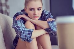 Adolescente deprimido solo infeliz en casa, ella se está sentando en el sofá y apoyado su cabeza con sus pies Fotos de archivo libres de regalías