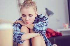 Adolescente deprimido solo infeliz en casa, ella se está sentando en el sofá y apoyado su cabeza con sus pies Fotos de archivo