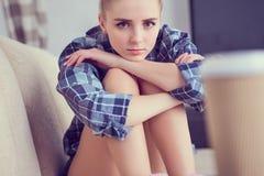 Adolescente deprimido solo infeliz en casa, ella se está sentando en el sofá y apoyado su cabeza con sus pies Fotografía de archivo