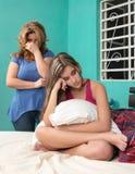 Adolescente desafiante con su madre que llora en el fondo Fotografía de archivo