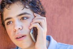 Adolescente desconcertado en el teléfono Foto de archivo