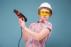 Adolescente desconcertante con un destornillador en las manos de incontrolable Fotografía de archivo